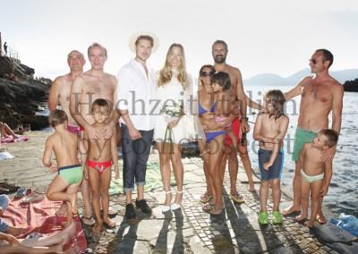 Unvergessliche Momente bei einer Strandhochzeit: Brautpaar mit Badegästen